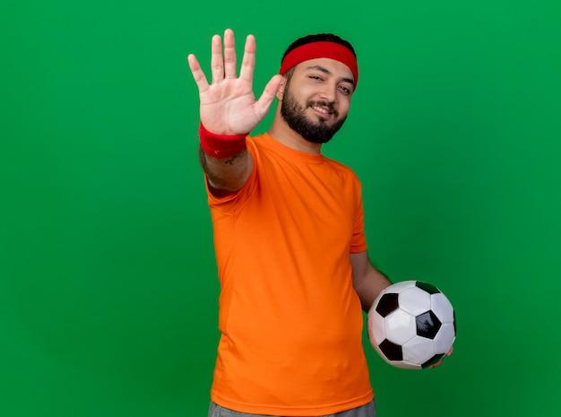 Lächelnder junger sportlicher mann, der stirnband und armband hält, das ball zeigt, der fünf lokalisiert auf grünem hintergrund mit kopienraum zeigt
