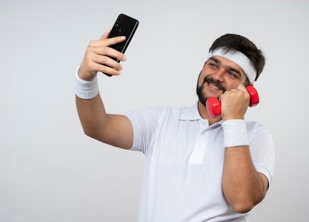 Lächelnder junger sportlicher mann, der stirnband und armband hält, die hantel halten, nehmen ein selfie lokalisiert auf weißer wand