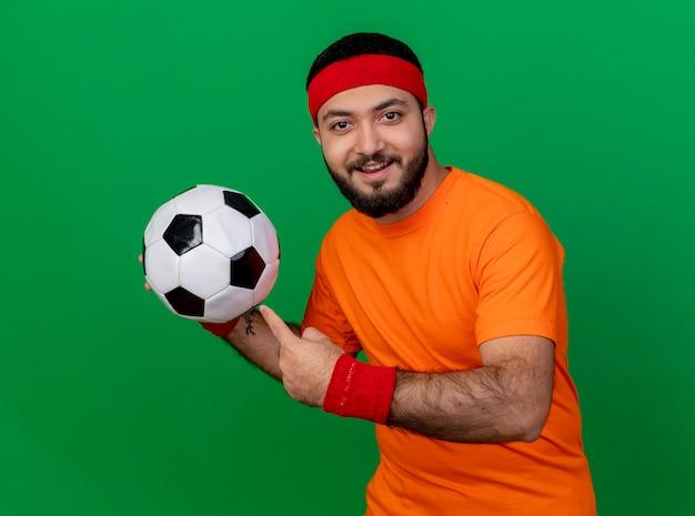 Lächelnder junger sportlicher mann, der stirnband und armband hält und punkte auf kugel lokalisiert auf grünem hintergrund trägt