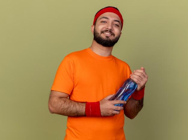 Lächelnder junger sportlicher mann, der stirnband und armband hält wasserflasche lokalisiert auf olivgrünem hintergrund