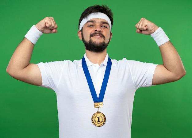 Lächelnder junger sportlicher mann, der stirnband und armband mit medaille trägt, die starke geste lokalisiert auf grün zeigt