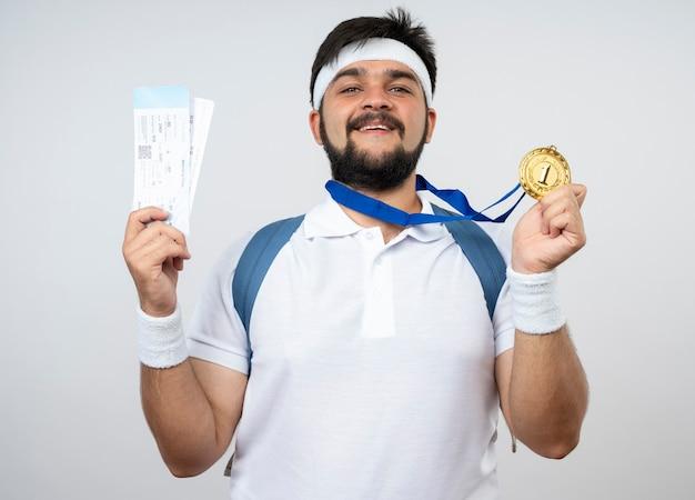 Lächelnder junger sportlicher mann, der stirnband und armband mit rucksack hält, der tickets mit medaille lokalisiert auf weißer wand hält