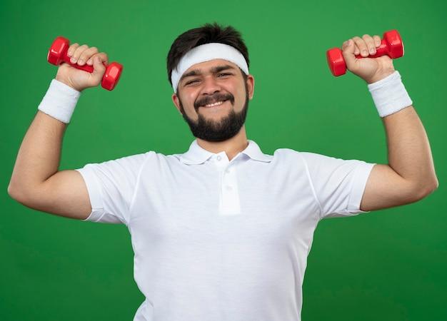 Lächelnder junger sportlicher mann, der stirnband und armband trägt, die mit hanteln trainieren, die auf grün lokalisiert werden