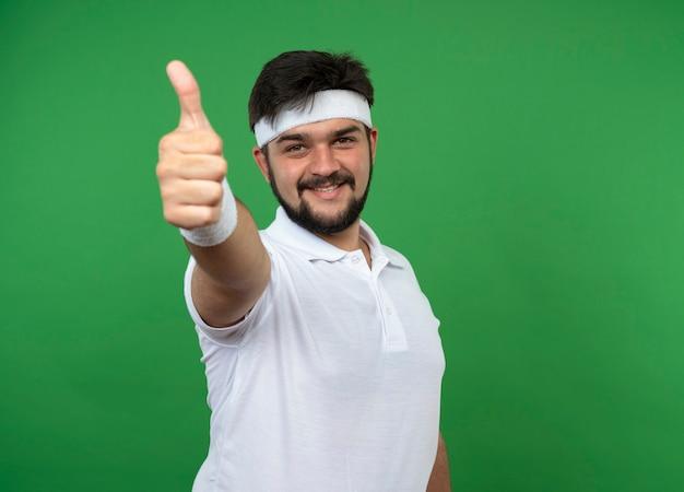 Lächelnder junger sportlicher mann, der stirnband und armband trägt, zeigt daumen oben lokalisiert auf grüner wand