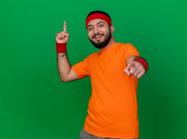 Lächelnder junger sportlicher mann, der stirnband und armband trägt, zeigt oben und an der kamera lokalisiert auf grün