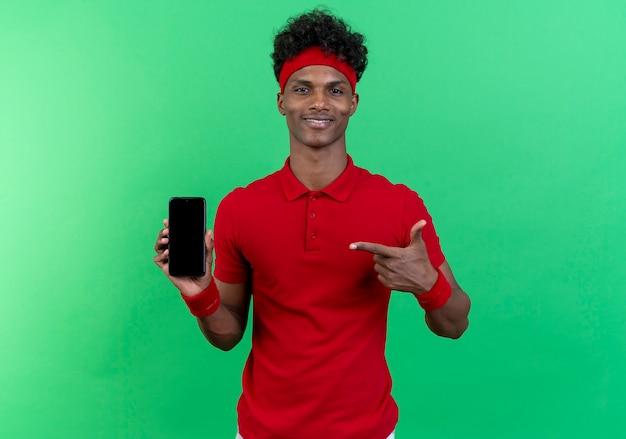 Lächelnder junger sportlicher mann, der stirnband und armband trägt