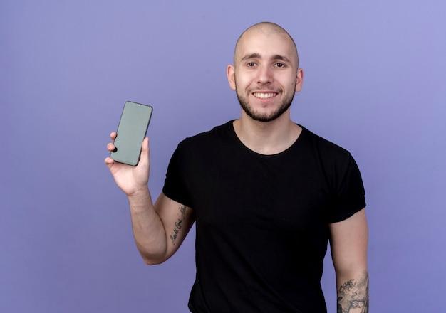 Lächelnder junger sportlicher mann, der telefon lokalisiert auf lila hält