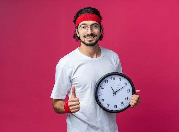 Lächelnder junger sportlicher mann mit stirnband mit armband, das die wanduhr mit daumen nach oben hält