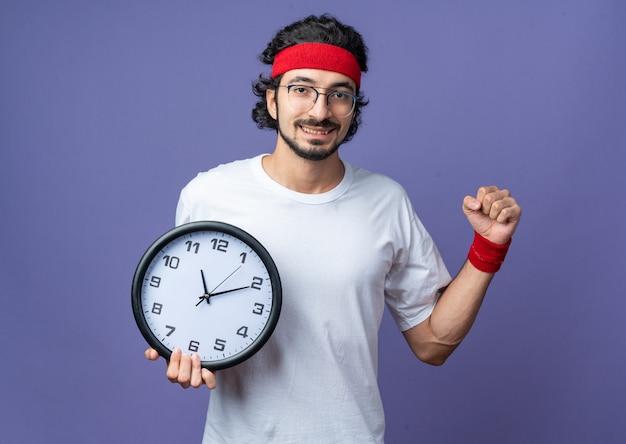 Lächelnder junger sportlicher mann mit stirnband mit armband, das eine wanduhr mit einer ja-geste hält