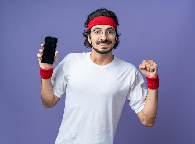 Lächelnder junger sportlicher mann mit stirnband mit armband, das telefon hält und ja-geste zeigt