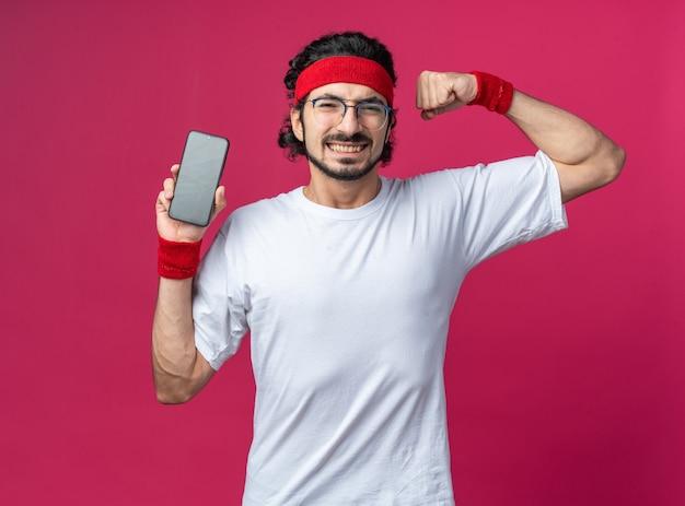 Lächelnder junger sportlicher mann mit stirnband mit armband, das telefon hält und starke geste zeigt