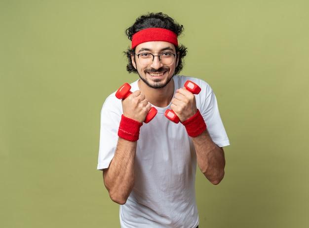 Lächelnder junger sportlicher mann mit stirnband mit armband, der mit hanteln trainiert