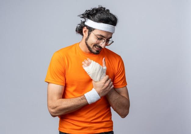 Lächelnder junger sportlicher mann mit stirnband mit armband mit verletztem handgelenk, das mit bandage umwickelt ist