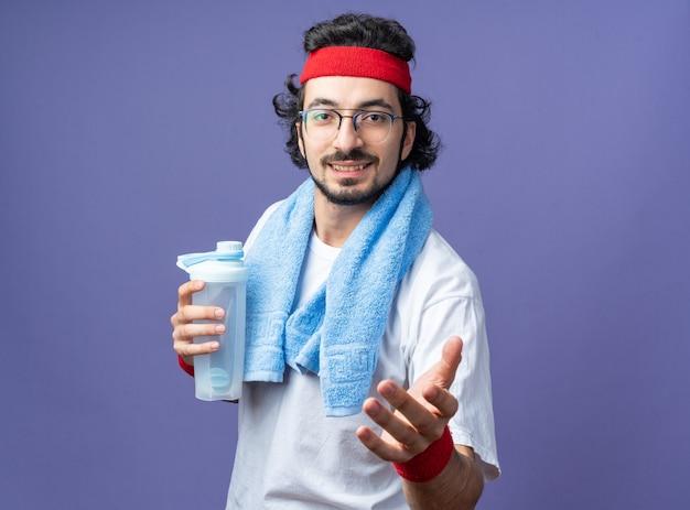 Lächelnder junger sportlicher mann mit stirnband mit armband und handtuch auf der schulter mit wasserflasche