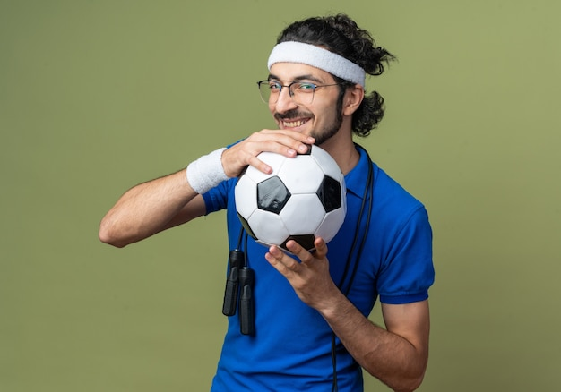 Lächelnder junger sportlicher mann mit stirnband mit armband und springseil auf der schulter mit ball