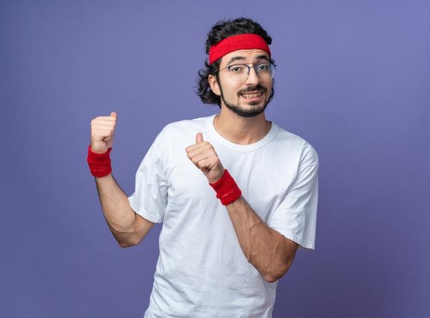 Lächelnder junger sportlicher mann mit stirnband mit armband zeigt hinten