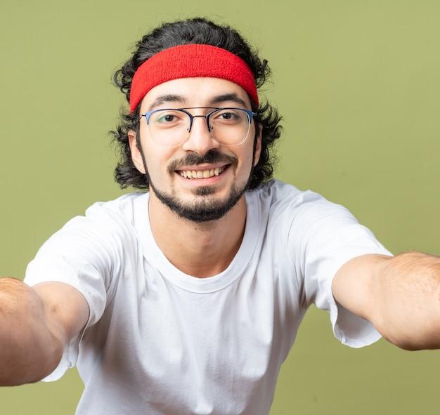 Lächelnder junger sportlicher mann mit stirnband
