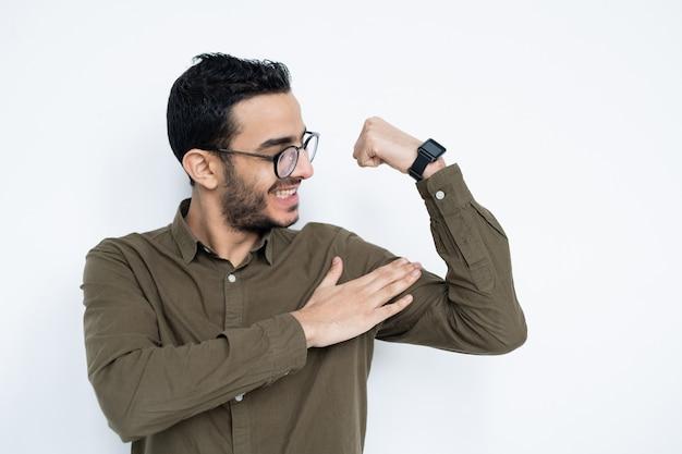 Lächelnder junger starker mann in brille und hemd, die seine muskeln berühren, während an weißer wand im studio stehen