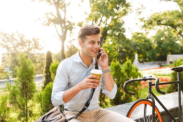 Lächelnder junger stilvoller mann, der auf handy spricht