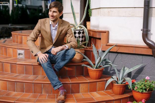 Lächelnder junger stilvoller mann, der draußen auf weinlesetreppe sitzt
