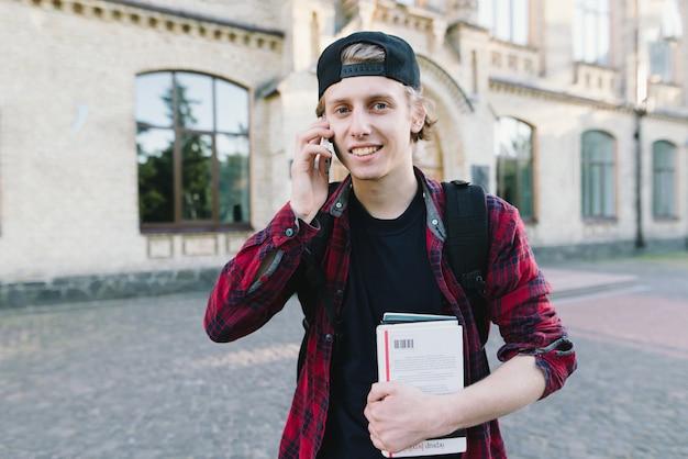 Lächelnder junger student mit büchern in seinen händen spricht per telefon