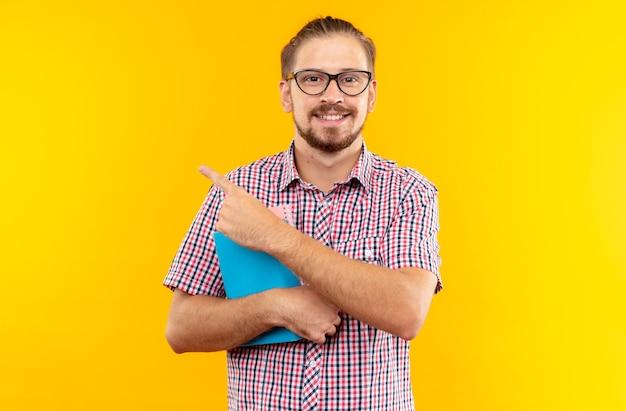 Lächelnder junger student mit rucksack mit brille, der buchpunkte an der seite hält, isoliert auf oranger wand mit kopierraum