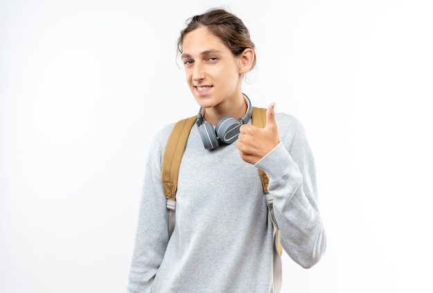 Lächelnder junger student mit rucksack mit kopfhörern am hals, der daumen nach oben zeigt