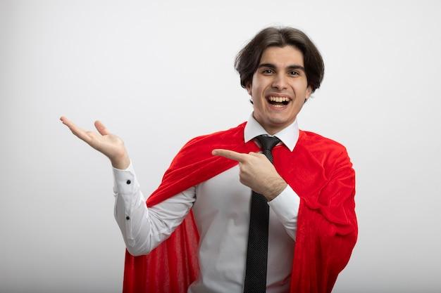 Lächelnder junger superheld, der krawatte trägt, die vorgibt zu halten, und auf etwas zeigt, das auf weiß isoliert ist