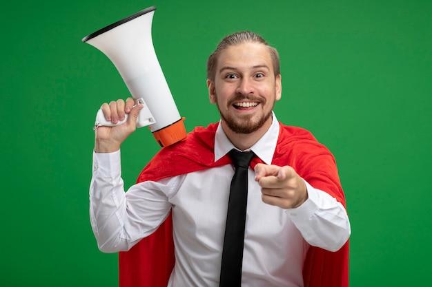 Lächelnder junger superhelden-typ, der krawatte trägt, die lautsprecher hält und sie geste lokalisiert auf grünem hintergrund zeigt
