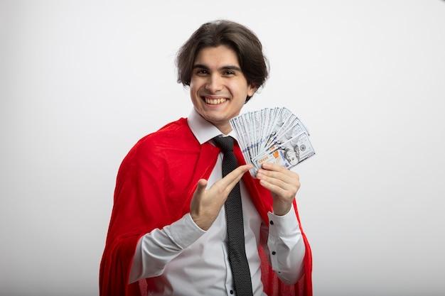 Lächelnder junger superheldenmann, der kamera betrachtet, die krawattenhaltung und punkte auf bargeld lokalisiert auf weiß trägt
