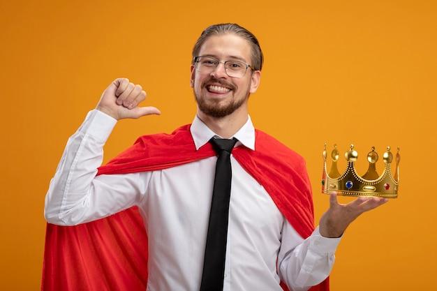 Lächelnder junger superheldenmann, der krawatte hält, die krone hält und daumen oben auf orange hintergrund zeigt