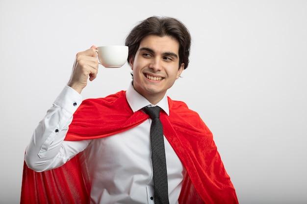 Lächelnder junger superheldenmann, der krawatte hält und tasse kaffee lokalisiert auf weißem hintergrund trägt