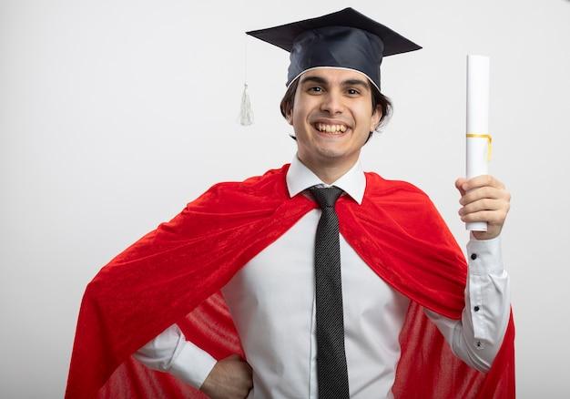 Lächelnder junger superheldenmann, der krawatte und graduiertenhut trägt diplom hält und hand auf hüfte legt
