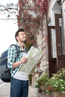 Lächelnder junger touristischer mann mit einer karte der stadt.