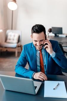 Lächelnder junger unternehmer, der am telefon im modernen büro spricht.