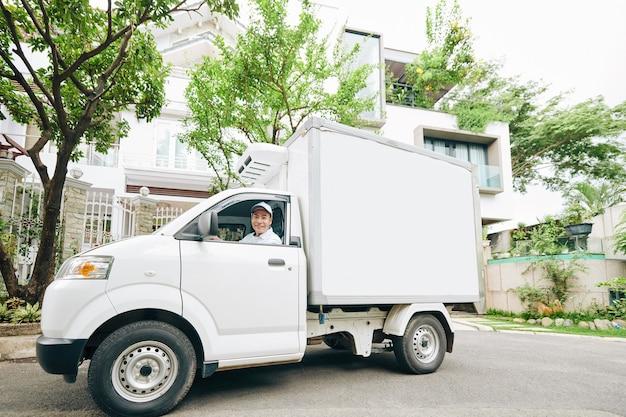 Lächelnder junger vietnamesischer mann, der milchwagen fährt und milchprodukte liefert