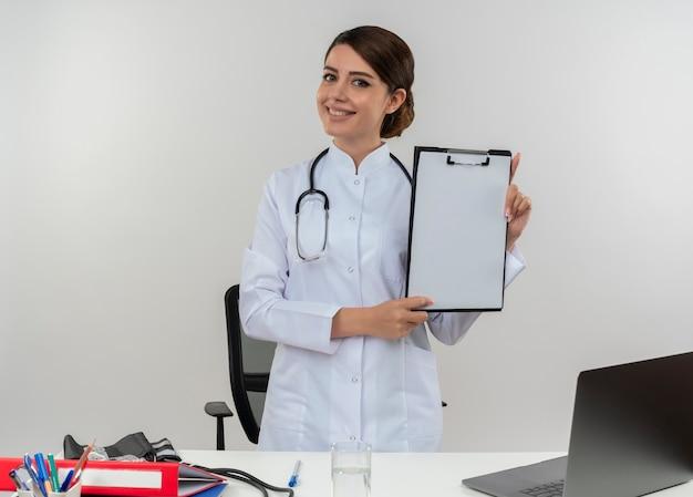 Lächelnder junger weiblicher arzt, der medizinische robe und stethoskop trägt, die hinter schreibtisch mit medizinischen werkzeugen und laptop halten, die zwischenablage lokalisiert auf weißer wand halten