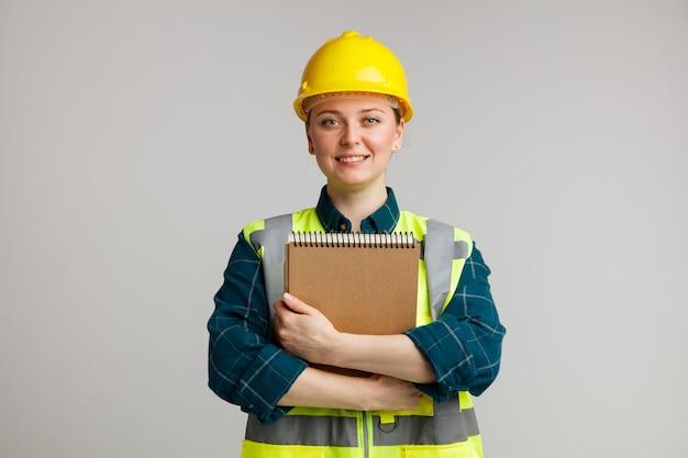 Lächelnder junger weiblicher bauarbeiter, der schutzhelm und sicherheitsweste trägt, die notizblock umarmen