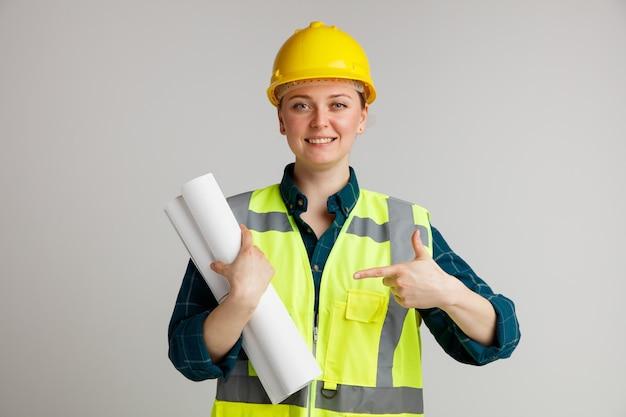Lächelnder junger weiblicher bauarbeiter, der schutzhelm und sicherheitsweste trägt und auf papiere zeigt