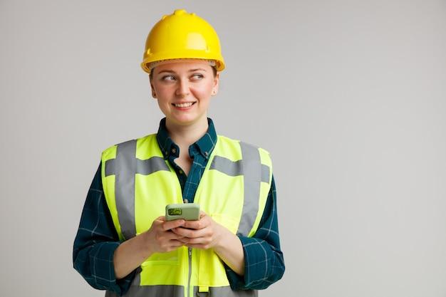 Lächelnder junger weiblicher bauarbeiter, der sicherheitshelm und sicherheitsweste hält, die handy mit beiden händen hält, die seite betrachten