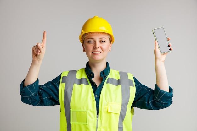 Lächelnder junger weiblicher bauarbeiter, der sicherheitshelm und sicherheitsweste hält, die handy zeigt, das oben zeigt