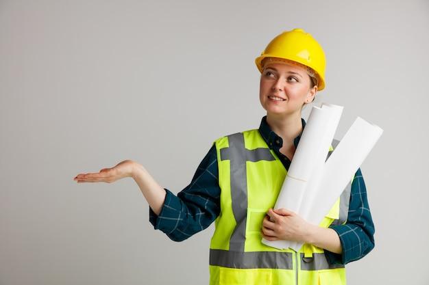 Lächelnder junger weiblicher bauarbeiter, der sicherheitshelm und sicherheitsweste hält, die papiere hält, die oben zur seite mit hand zeigen