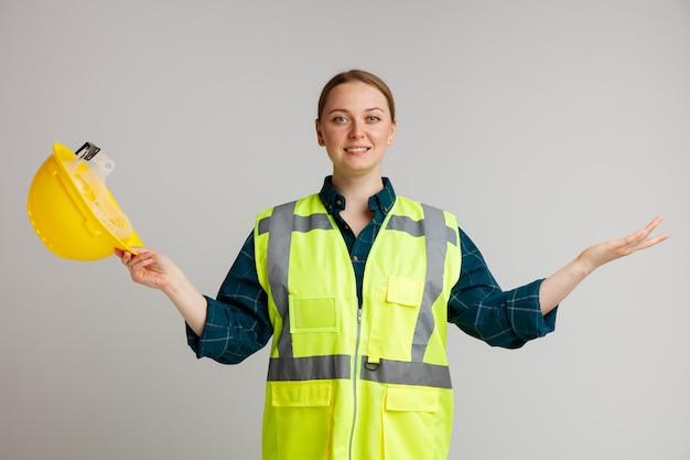 Lächelnder junger weiblicher bauarbeiter, der sicherheitsweste hält, die sicherheitshelm hält, der leere hand zeigt