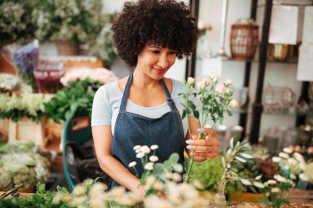 Lächelnder junger weiblicher florist, der blumen im shop anordnet