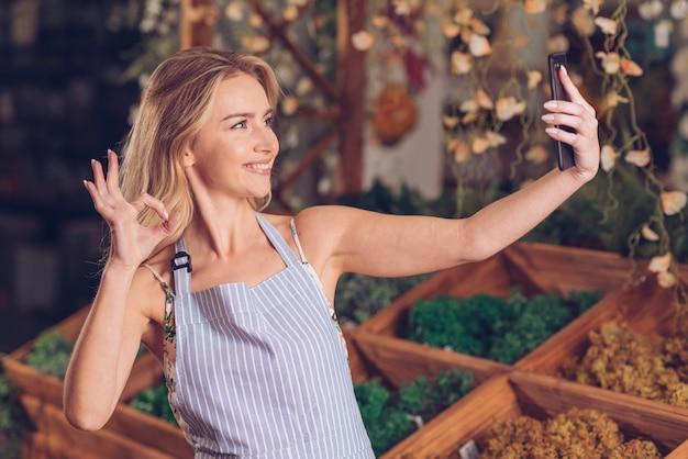 Lächelnder junger weiblicher florist, der selfie am intelligenten telefon zeigt okaygeste im shop nimmt