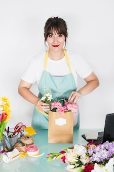 Lächelnder junger weiblicher florist mit blumenpapiertüte auf schreibtisch