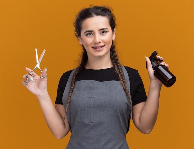 Lächelnder junger weiblicher friseur in uniform, die schere mit sprühflasche lokalisiert auf orange wand hält