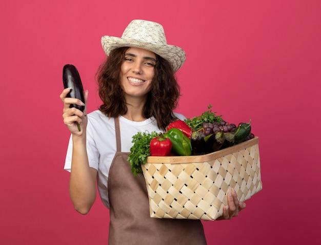 Lächelnder junger weiblicher gärtner in der uniform, die gartenhut hält, der gemüsekorb mit aubergine hält