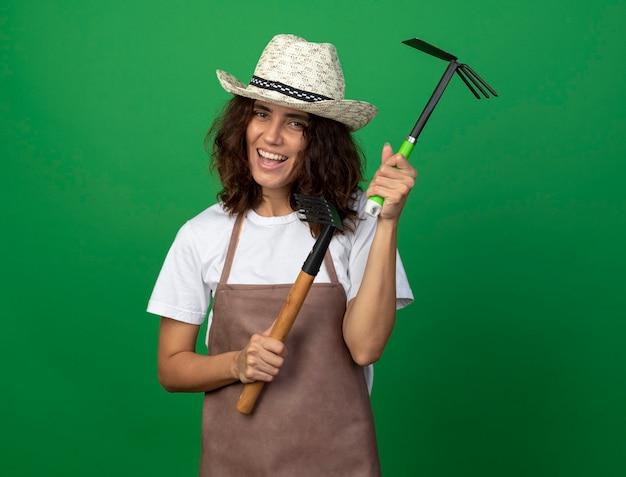 Lächelnder junger weiblicher gärtner in der uniform, die gartenhut hält, der rechen mit hacke hält