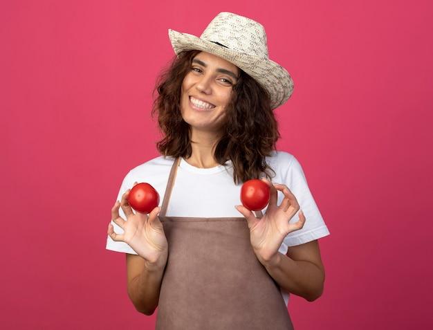 Lächelnder junger weiblicher gärtner in der uniform, die gartenhut hält, der tomaten isoliert auf rosa hält